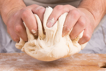 Baker holds raw dough in hands