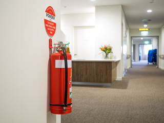 Dry chemical powder fire extinguisher and sign in corridor