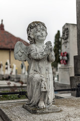 Angel watching over a tombstone. Cemetery figurine. Aged marble