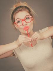 Happy woman holding fake lips on stick