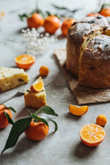 Panettone, traditional Italian Christmas cake - shallow depth of field close-up with sliced oranges.