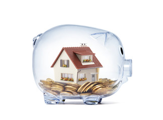 House on money inside transparent piggy bank with clipping path