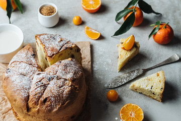 Panettone, traditional Italian Christmas cake. Close-up with slice and oranges.