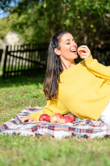 A beautiful woman eating a Apple in the Garden in Autumn