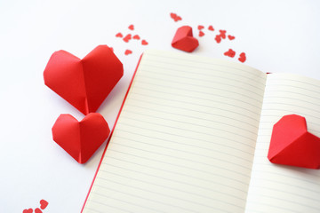 Red Paper hearts of origami with a notebook on a white background