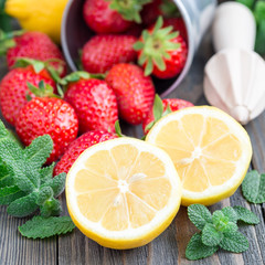 Ingredients for homemade strawberry lemonade on a wooden table, square format