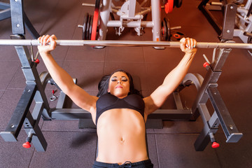 A weightlifting young woman in the gym