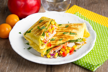 Mexican burritos with tortilla, chicken, corn, tomatoes, onion, spicy traditional dish, tasty food
