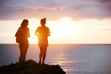 Two girls travel sea sunset concept