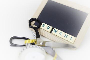 Schneiden Sie gut bei der nächsten Betriebsratswahl ab! Eine Schreibtafel mit Schere und Massband.