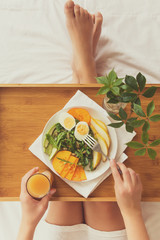 Healthy eating concept. Woman having breakfast in bed. Top view.