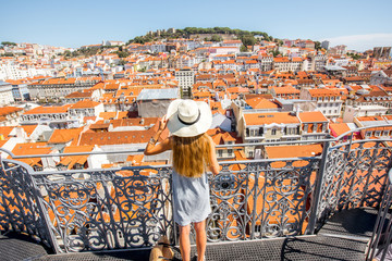 Young woman tourist enjoying beautiful cityscape top view on the old town during the sunny day in Lisbon city, Portugal