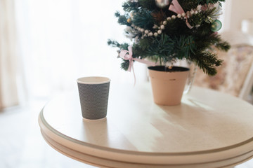 Brown paper coffee Cup in the coffee shop on a wooden table next to the vase. Coffee to go