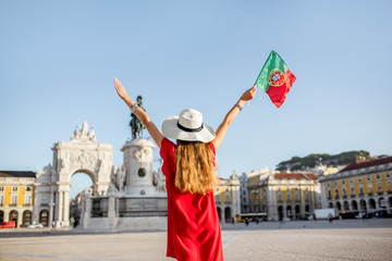 Lifestyle portrait of a young woman tourist with portuguese flag standing on the main square during the morning light in Lisbon city, Portugal