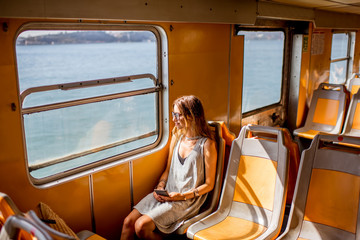 Young woman traveling in the old ferry enjoying view on the sea from the window