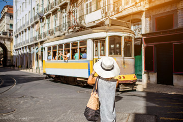 Young woman tourist photographing famous retro yellow tram traveling in Lisbon city, Portugal