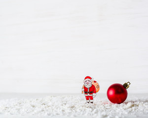 New Year's background. The figure of Santa Claus is made of paper. Billet for postcards or congratulations. In the forest among the snowdrifts.