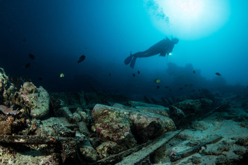 scuba diver over the wooden wreck of a diving boat with tanks in Maratua