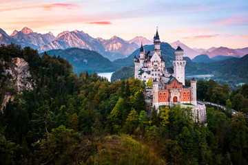 Foto op Plexiglas Kasteel The famous Neuschwanstein castle during sunrise, with colorful panorama of Alps in the background