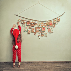 child in pajamas and Christmas cap stretches for advent calendar with small gifts