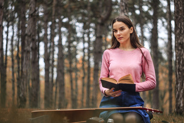 young beautiful girl with a book in the autumn forest and guitar
