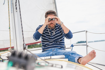 man sits on sailing yacht and looks through binoculars