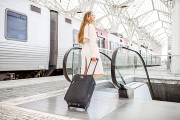 Young and elegant woman walking with luggage near the train at the modern railway station