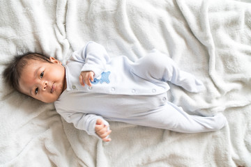 Cute asian baby liyng on bed
