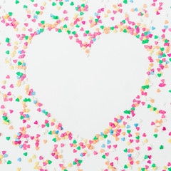 Heart symbol made of colorful bright confetti on white background. Flat lay, top view copy space. Love concept