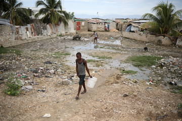 A man carries an empty bucket as he walks towards a water reservoir in Port-au-Prince