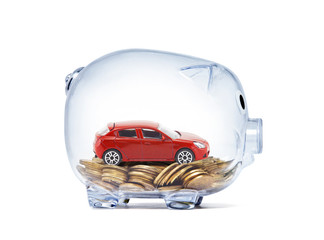 Red car on money inside transparent piggy bank with clipping path