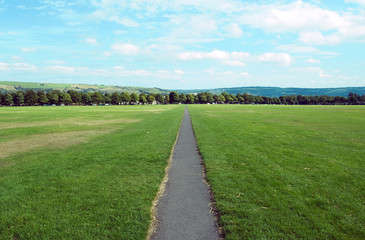 long straight foortpath ina park with grass lawn and distant trees in halifax yorkshire