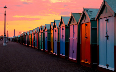 A row of 30 colourful beach beach huts in a line, with a diminishing perspective, all the beach huts have different color doors it is sunset and the  light is very colourful