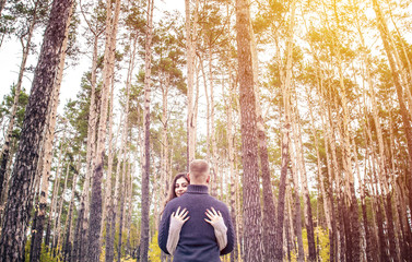 A beautiful girl stands embracing with a guy against the trees. Loving young couple. St. Valentine's Day.