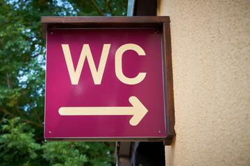 Hinweis auf eine öffentliche Toilette an der Fassade eines Hauses