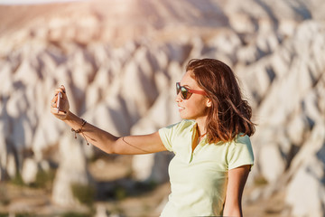 Happy young woman taking selfie with her smartphone with Cappadocia landscape at the background, Goreme, Turkey