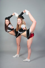 Two Cheerleaders Performing A Scorpion