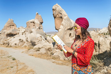 A happy young tourist eastern asian girl in traditional clothes travels among cappadocia landscape and cave towns at summer and reading map