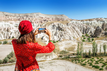 A tourist eastern asian girl makes a photo on the phone in beautiful valley in Cappadocia in Turkey.