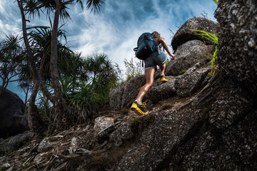 Woman hiker with backpack climbs steep rocky terrain