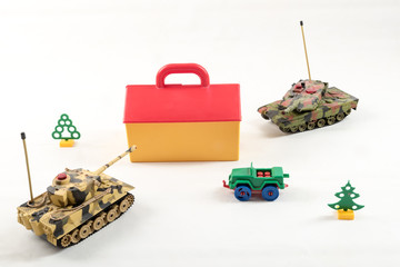 Plastic toy tanks attacked a toy house. A re-enactment. War, aggression.