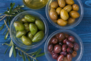 Bowls with different olives on color wooden background