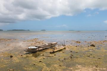 Abandoned old outrigger canoe on shallow water, Tongatapu Island, Tonga