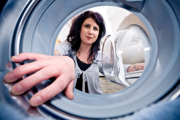 Woman Looking Into A Washing Machine
