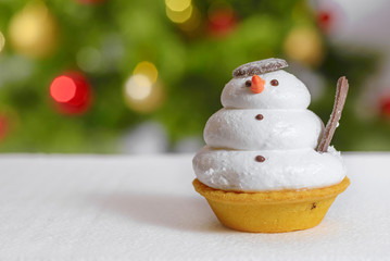 Snowman cookie and christmas tree behind