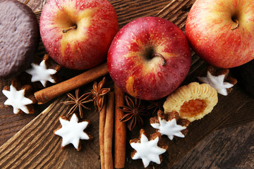christmas cookies, apples, gingerbread and spice on brown background