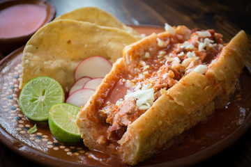 Authentic Mexican torta ahogada pork meat sandwich soaked in hot tomato sauce with lime and crispy tacos