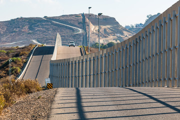The international border wall between San Diego, California and Tijuana, Mexico, with an approaching Border Patrol vehicle on a nearby hill.