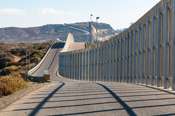 The international border wall between San Diego, California and Tijuana, Mexico, as it begins its journey from the Pacific coast and travels over nearby hills.