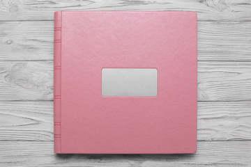 pink photobook with  leather jacket cover and shield photoalbum with a hard cover on a wooden surface